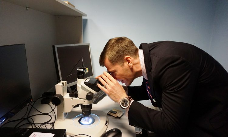 A man bent over to look through a microscope