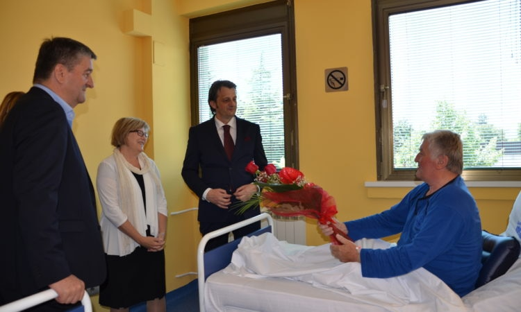 Ambassador and two men visiting a person handing flowers to the Ambassador in a hospital
